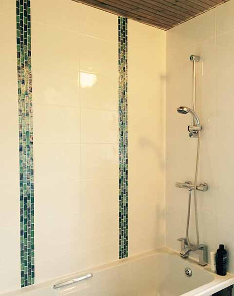 330 x 250 mm bumpy white ceramics with four glass mosaic strips installed vertically either side of the hand basin and bath wall